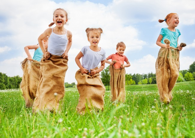 Five kids jump in sacks on a dandelion meadow on summer hot day